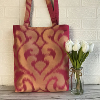 Hot pink tote bag with a shiny gold scrolled pattern