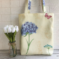 Floral tote bag in pale yellow with a stem of blue flowers and pink butterfly