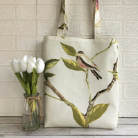 Bird tote bag with a cream, red and black bird perched on a leafy branch