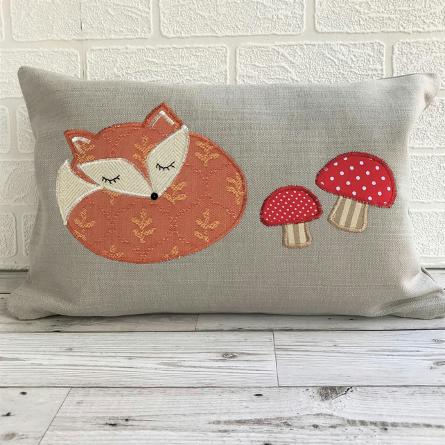 Sleepy fox cushion in pale taupe with terracotta fox and red toadstools
