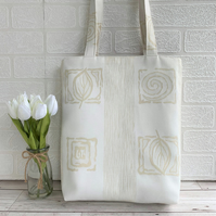 Cream tote bag with elegant pattern of golden beige tile motifs