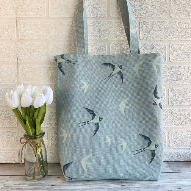 Blue tote bag with swallows in flight print pattern