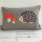 Hedgehog cushion with brown floral hedgehog and red polka dot toadstools