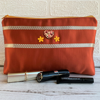 Large make up bag in burnt orange satin trimmed with ribbon and buttons