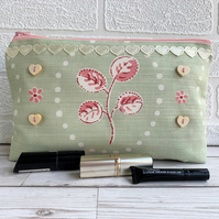 Large make up bag in pale green and pink print fabric with ribbon and buttons