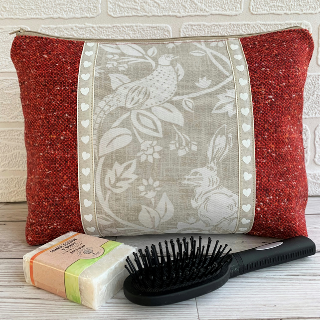 Red toiletry bag with decorative panel featuring a pheasant and hare
