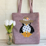 Penguin tote bag in lilac with a floral penguin in a straw sunhat