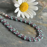 Beaded daisy chain bracelet in teal and purple colours