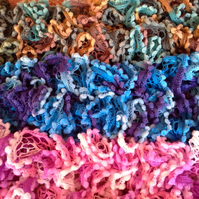 Hand Knitted ruffle scarf with pompom edging.