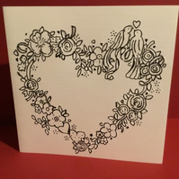 Embossed card featuring two love. Irds in a heart