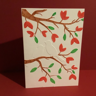 Coloured, embossed card with 2 birds perched in a tree. JM046
