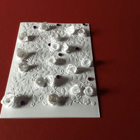 A white card with white flowers and purple beads CC063