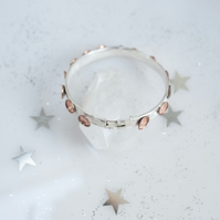 Oval sterling silver bracelet with copper rings