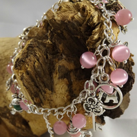 Silver plated charm bracelet with pink cats eye beads