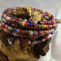 Memory wire bracelet with multi coloured glass seed beads and heart charms