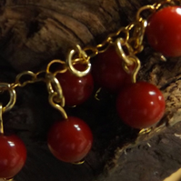 Red coral beaded bracelet with brass gold plated heart chain