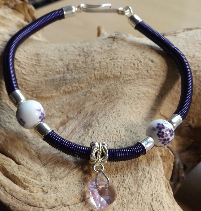 Gizmo purple coiled bracelet with porcelain flower beads with pink crystal heart