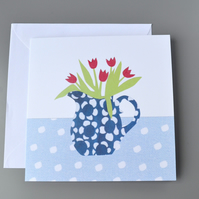 Jug of red tulips in a blue and white patterned jug on spotty tablecloth card