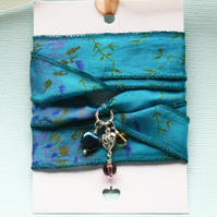 Blue green patterned silk ribbon wrap bracelet with heart and glass charms