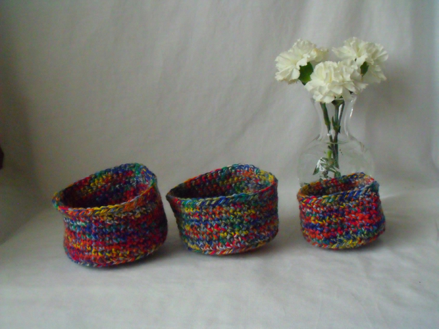 set of three multi coloured crocheted stackable craft storage tubs