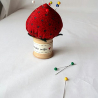 novelty strawberry pin cushion on a vintage wooden bobbin