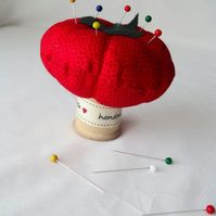novelty tomato pin cushion on a vintage wooden bobbin