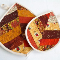 pair of leaf shaped pot holders in autumn colours,  patchwork quilted coasters