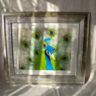 large framed peacock embroidery in a silver frame