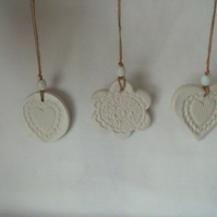 set of three impressed ceramic hanging decorations, unpainted