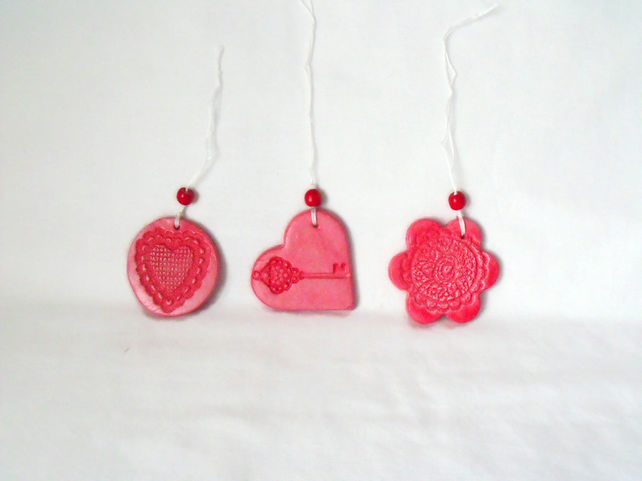 set of three impressed ceramic hanging decorations in red