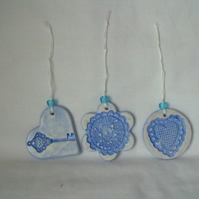 set of three impressed ceramic hanging decorations in blue