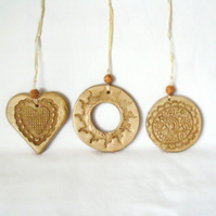 set of three impressed ceramic hanging decorations in beige