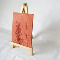 terracotta impressed clay tile displayed on an easel, 3 x 5 inches