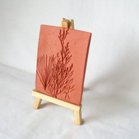 terracotta impressed clay tile displayed on an easel, number 2 of 8 available