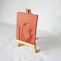 terracotta impressed clay tile displayed on an easel, number 3 of 8 available