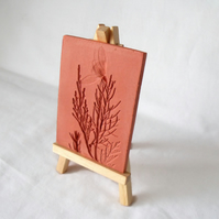 terracotta impressed clay tile displayed on an easel, number 4 of 8 available