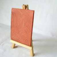 terracotta impressed clay tile displayed on an easel, number 6 of 8 available