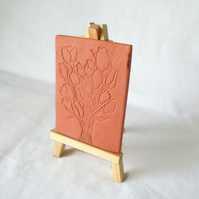 terracotta impressed clay tile displayed on an easel, floral design