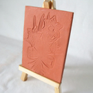 terracotta impressed clay tile displayed on an easel, daffodil design