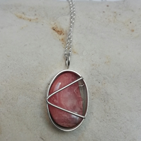 Polished Rhodochrosite in an Oval Cage.