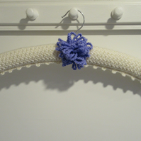 Ladies knitted coat hanger with a large allium flower