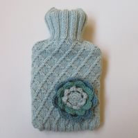 Knitted Ice blue trellis stitch hot water bottle cover with crocheted flower