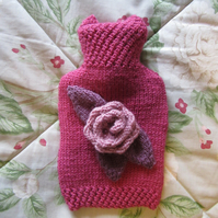 Hand knitted raspberry 'n' rose hot water bottle cover
