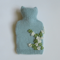 Hand knitted blue ditsy hot water bottle cover