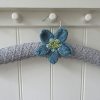 Hand knitted padded coat hanger with blue poppy flower
