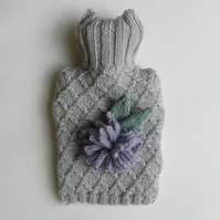 Hand knitted silver coloured hot water bottle with lilac allium flower