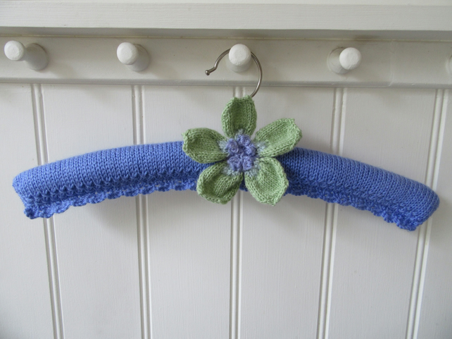 Hand knitted padded coat hanger with a knitted anemone flower