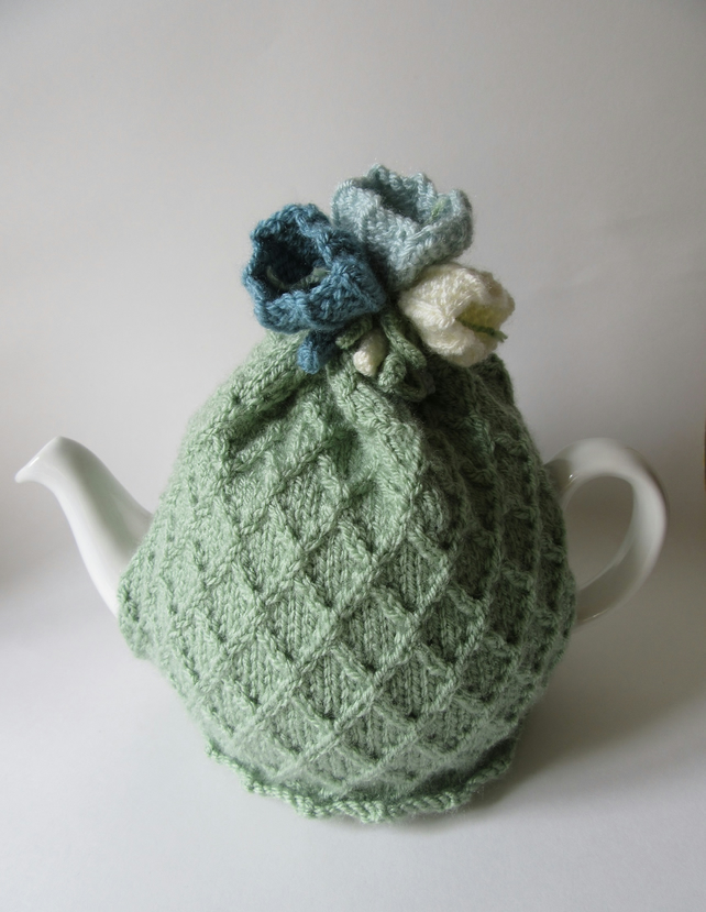 Hand knitted pastel green tea pot cosie with crocus flowers