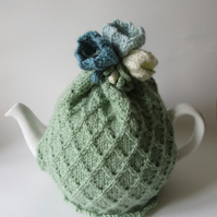 Hand knitted green tea cosie with crocus flowers