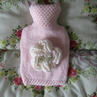 Pink hand knitted hot water bottle with a large peony flower